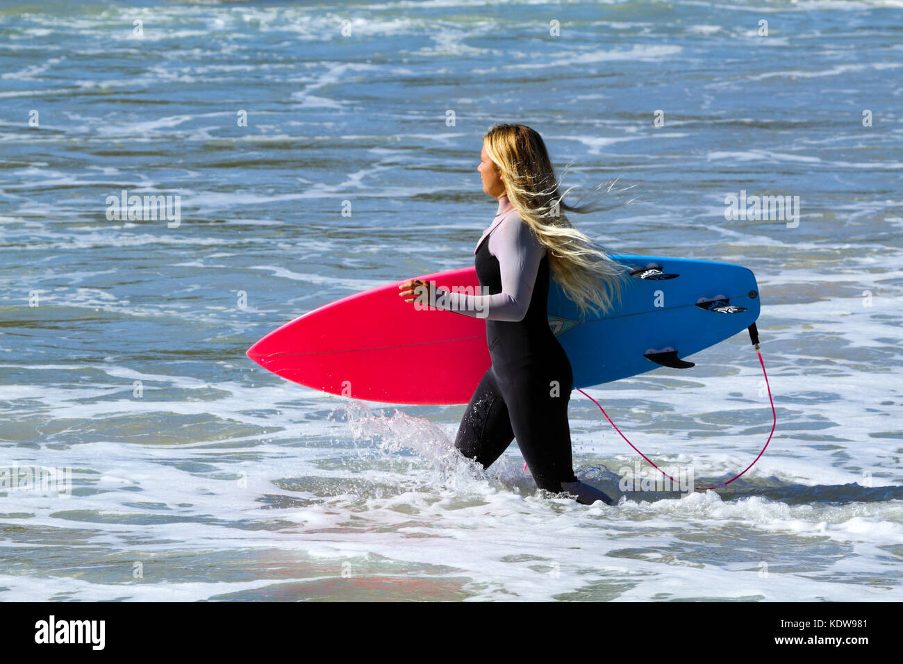 A blond lady in her early twenties wades into the surf with surfboard - Stock Image