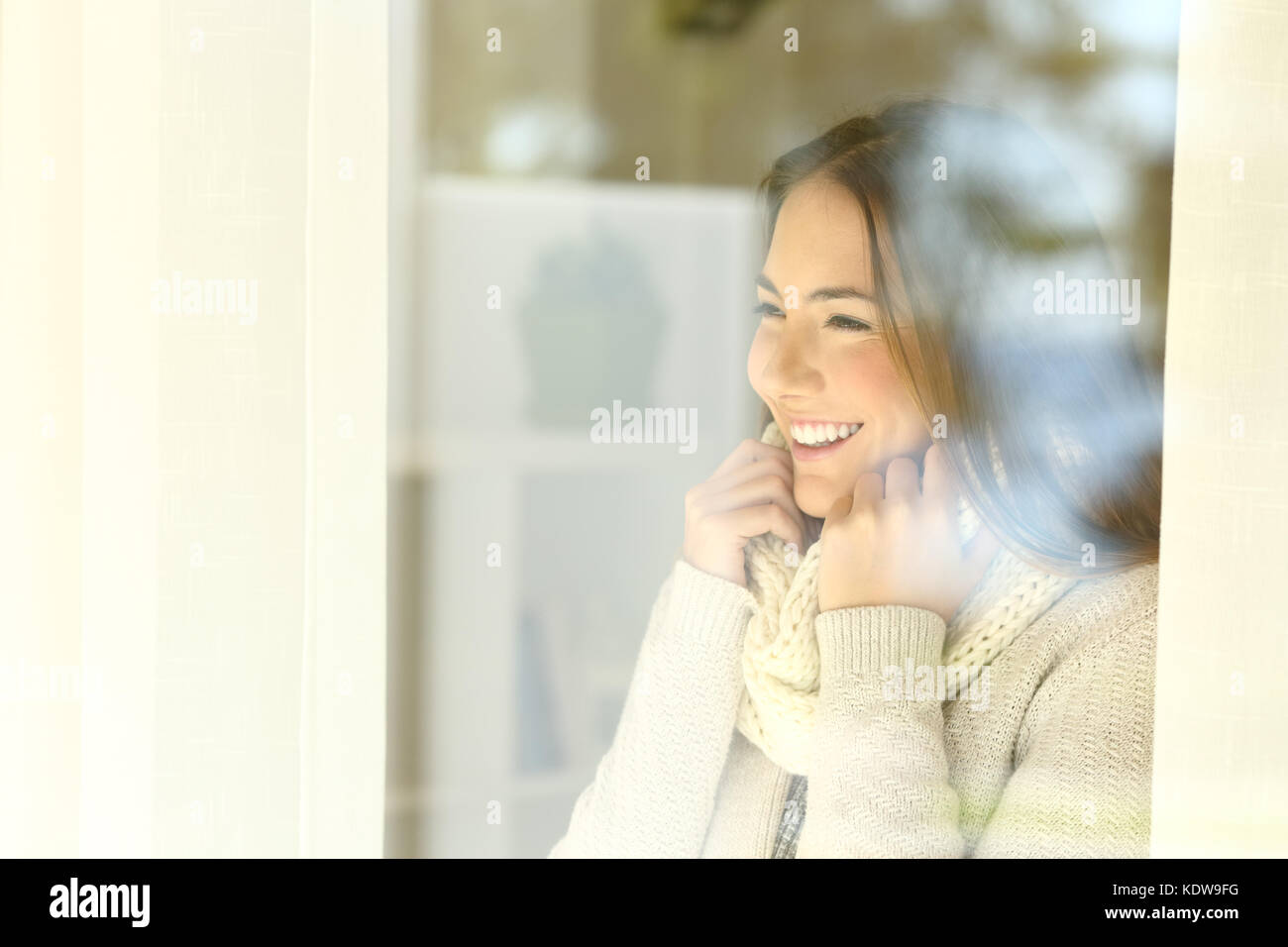 Happy woman warmly clothed looking outside through a window in winter at home or hotel room - Stock Image