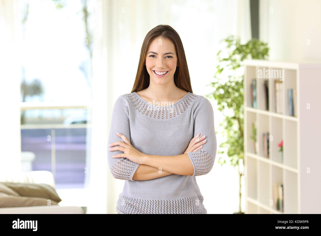 Portrait of a proud homeowner posing looking at you standing in the living room at home - Stock Image