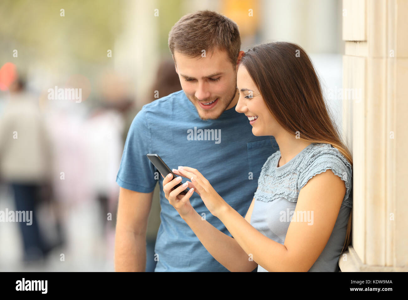 Happy casual couple checking content in a smart phone standing on the street - Stock Image