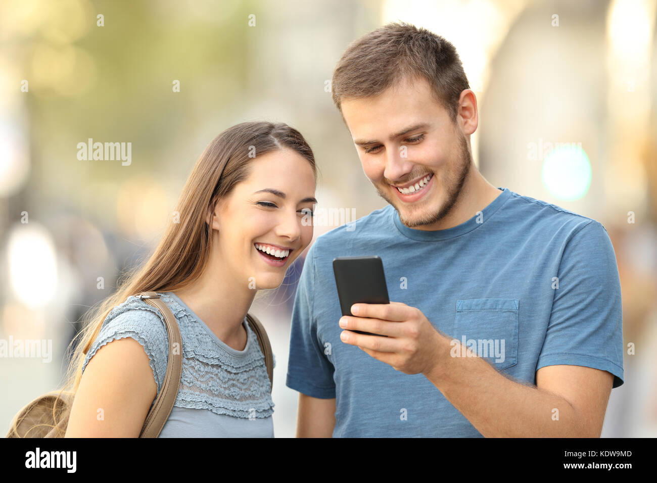 Happy couple enjoying using a smart phone standing on the street - Stock Image