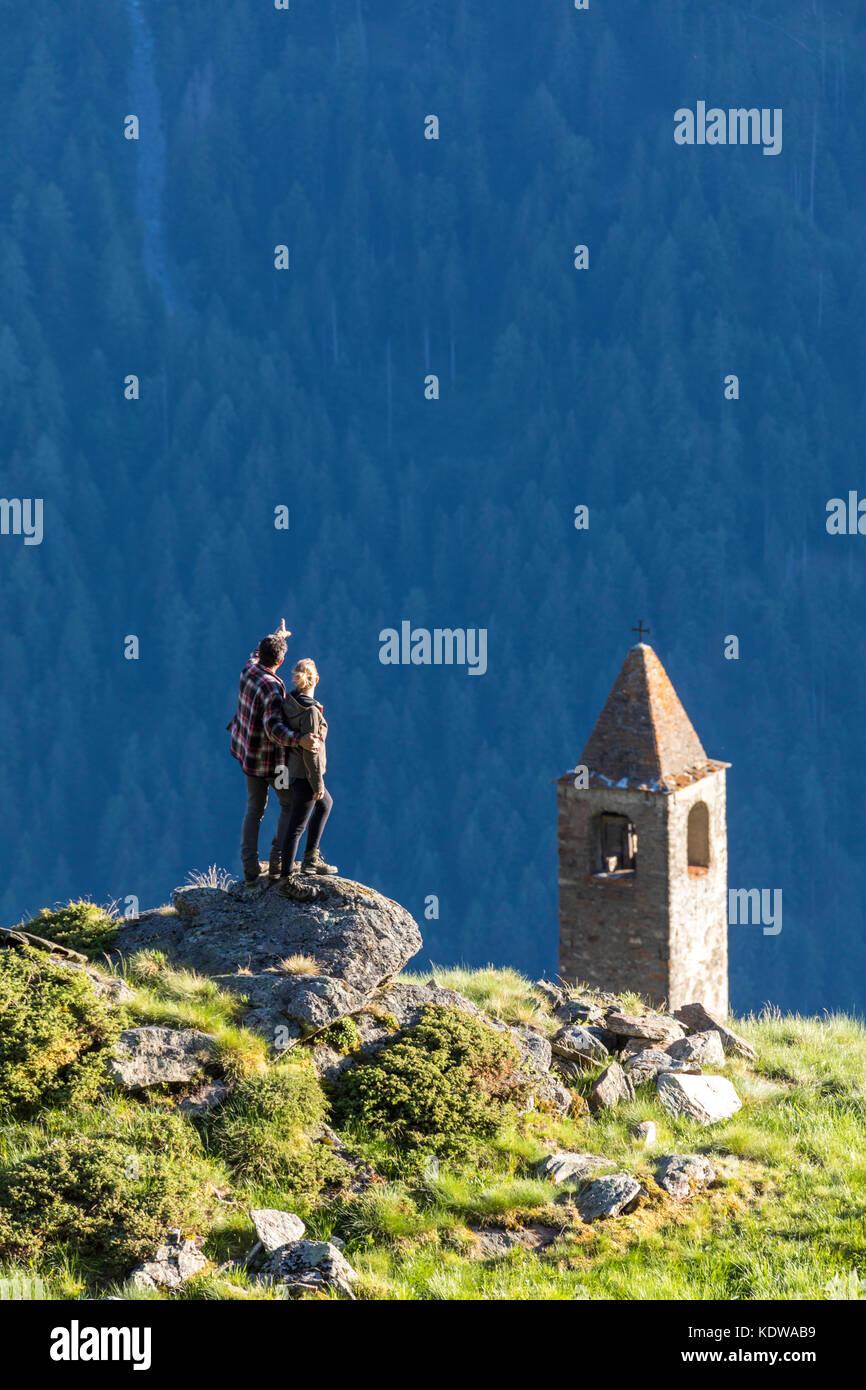 Man and woman embraced look the bell tower, San Romerio Alp, Brusio, Canton of Graubünden, Poschiavo valley, Switzerland Stock Photo