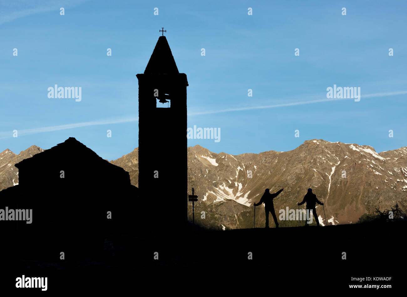 Silhouettes of hikers at the old church at dawn, San Romerio Alp, Brusio, Canton of Graubünden, Poschiavo valley, - Stock Image