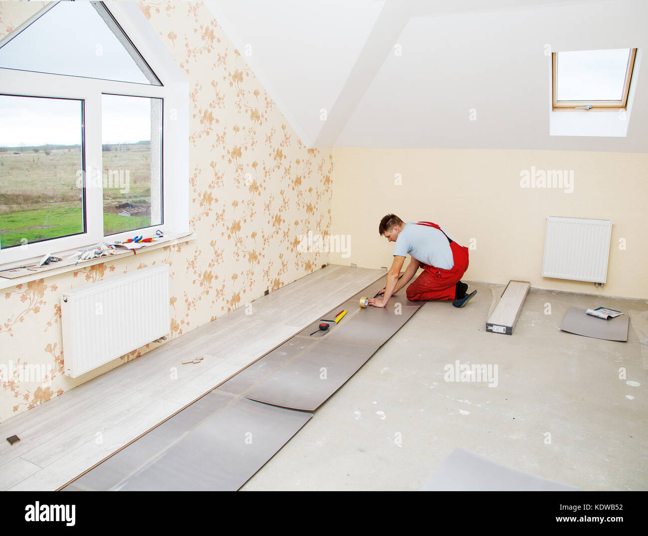 handyman laying down laminate flooring boards while renovating a house - Stock Image