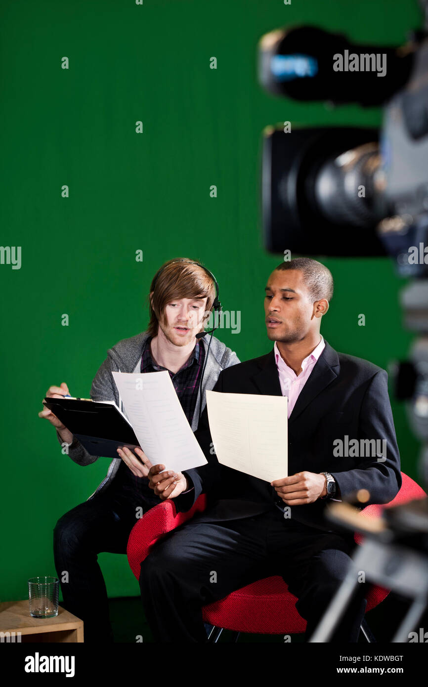 Floor manager runs through scripts with a Television Presenter in a green screen studio. TV camera out of focus - Stock Image