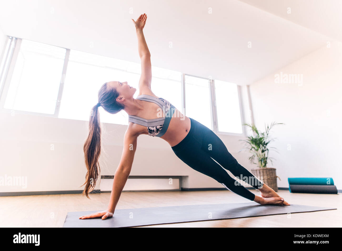 Slim woman in side plank pose at yoga class, Vasisthasana exercise. Female balancing on mat indoors at fitness gym - Stock Image