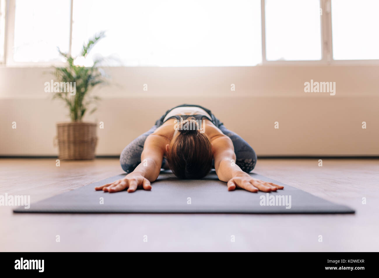 Fit woman performing child yoga pose at gym class. Fitness woman working out on yoga mat indoors. Stock Photo