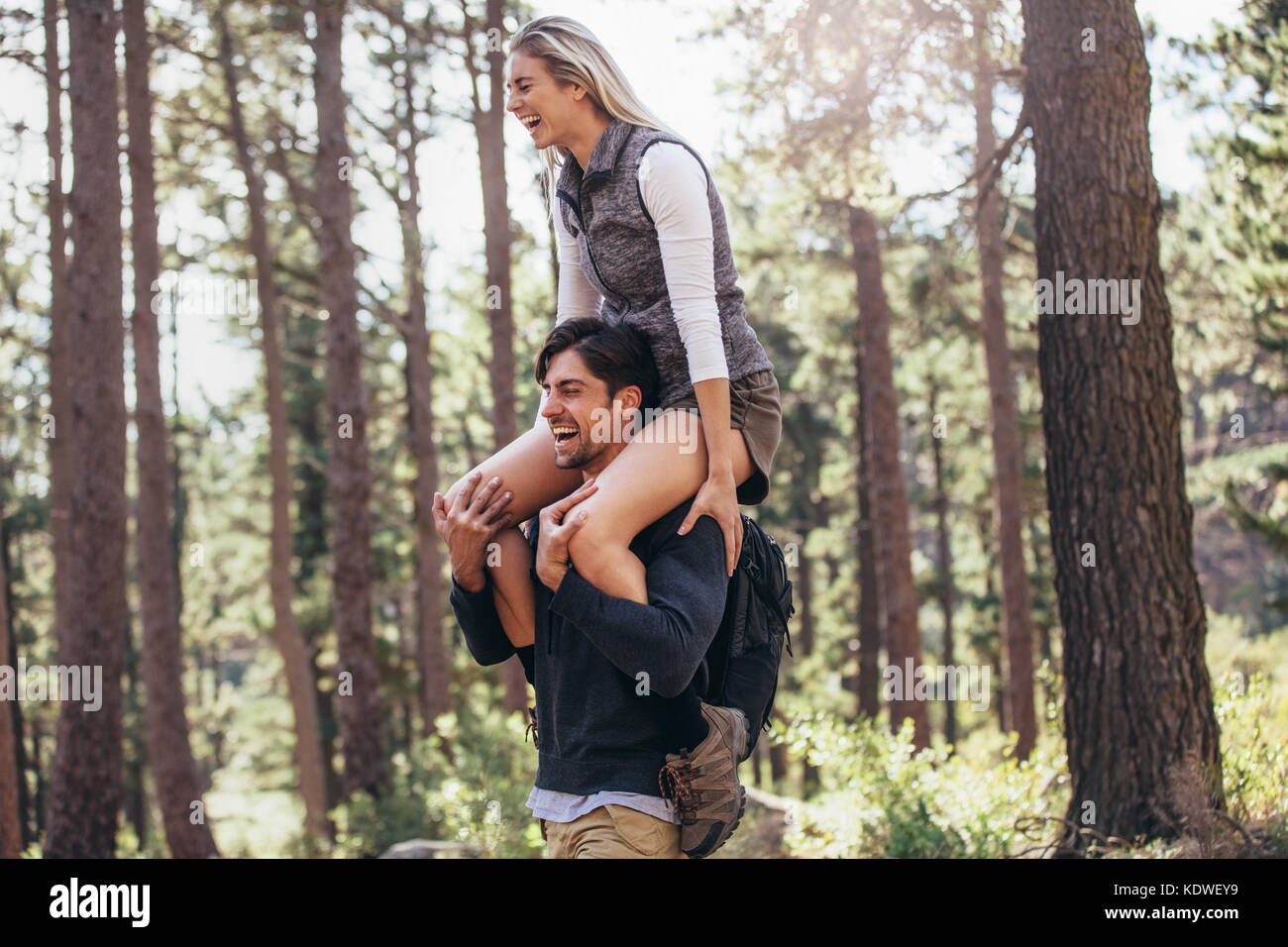 Hiking couple having fun while trekking in forest. Woman riding piggyback on man during hiking in forest. - Stock Image
