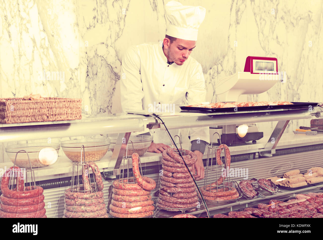 Smiling adult shop-boy in working clothes taking raw meat from stall - Stock Image