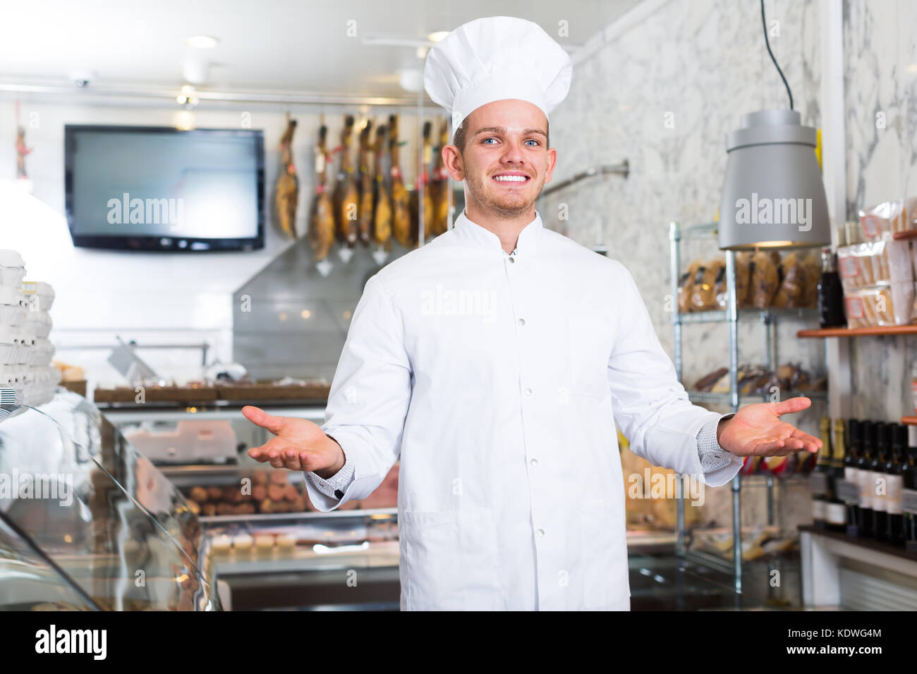 Laughing ordinary male seller working at meat market - Stock Image
