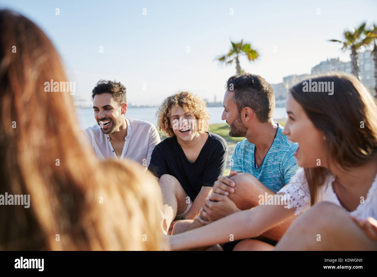 Portrait of happy friends sitting outside together laughing - Stock Image