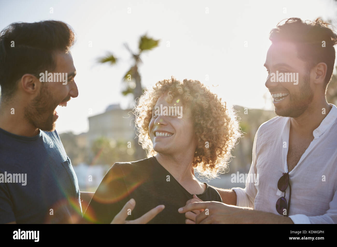 Portrait of three happy men standing together outside laughing - Stock Image