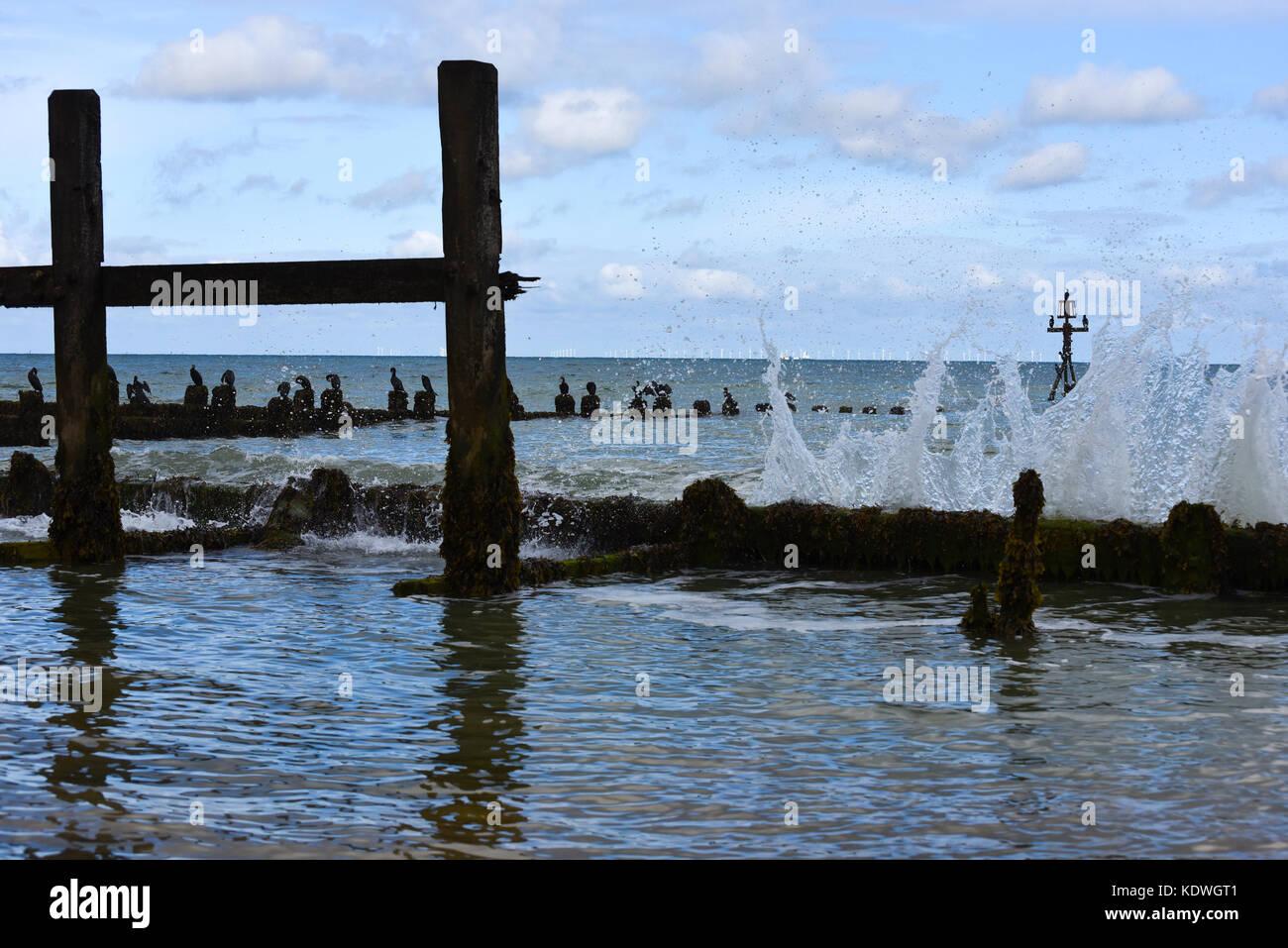 The North Sea Breaking against Storm Breakers in Norfolk. - Stock Image