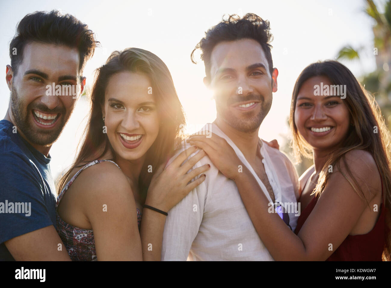 Portrait of four happy friends standing together outside in sunlight - Stock Image