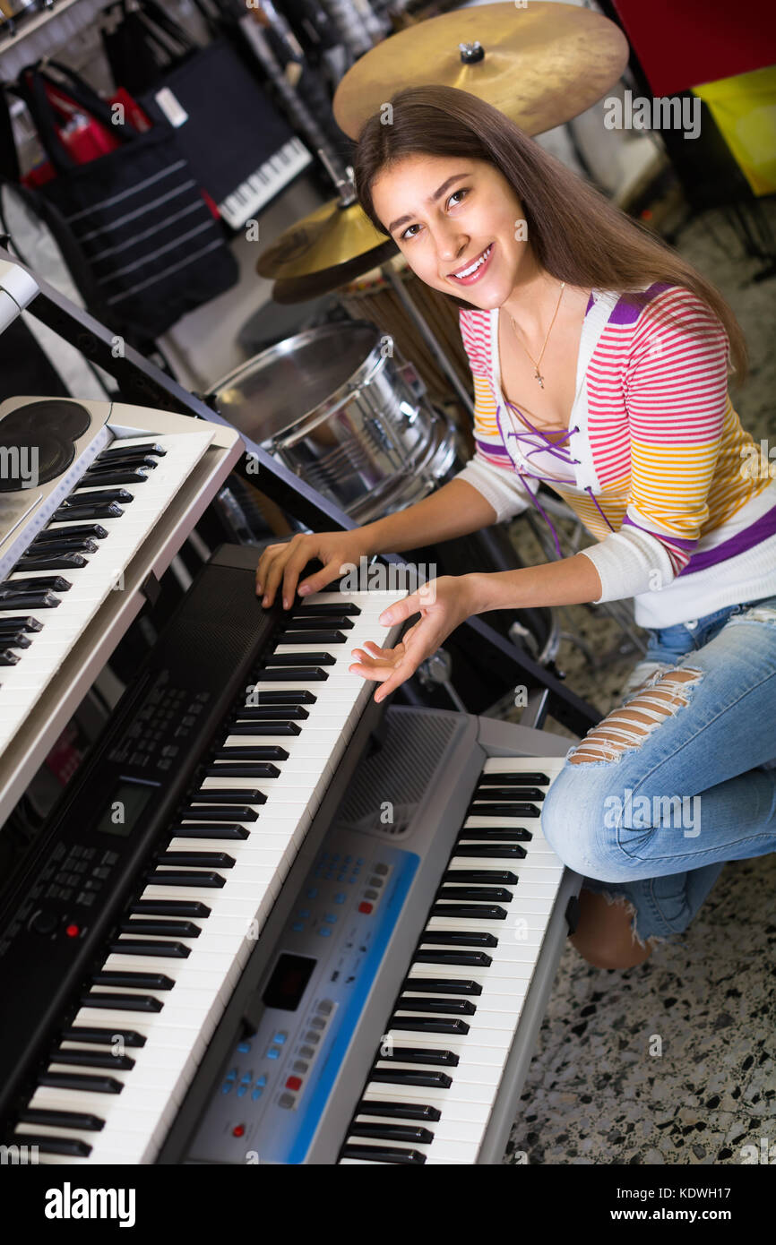 Smiling longhaired teenage girl choosing synthesizer in store - Stock Image