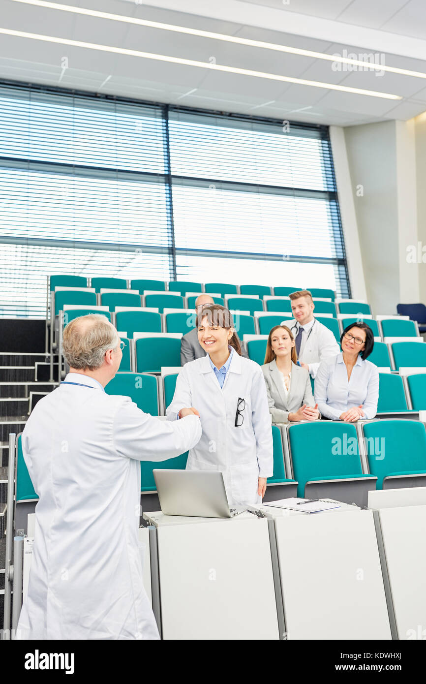 Professor congratulate student for successful medical school exam - Stock Image