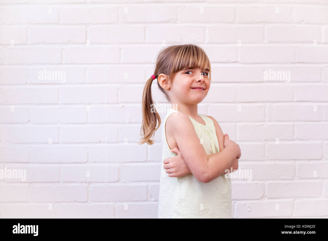 Attractive little blonde girl child profile half length portrait. Cute kid with arms folded against white brick - Stock Image