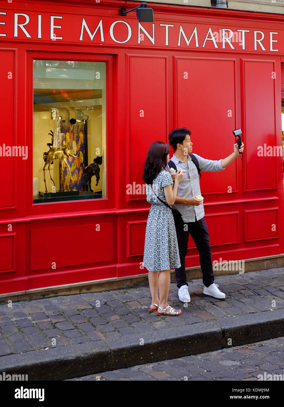 A young tourist couple take a selfie or shoot video using their gopro camera in Montmartre, Paris Stock Photo