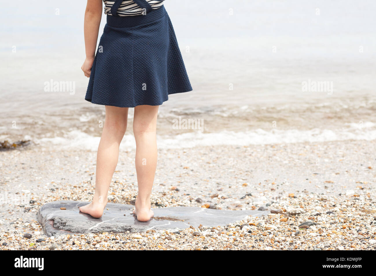 Little girl standing on pebble beach at sea shore. Lower body of female child at the beach. - Stock Image