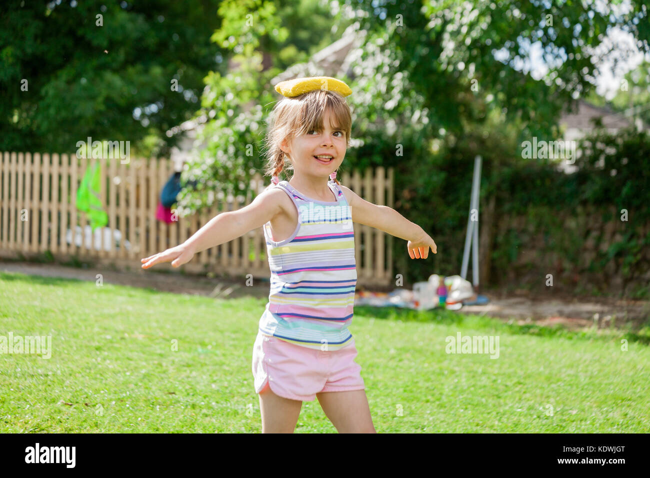 Pretty elementary age little girl on sports day balancing yellow bean bag on head. Happy fun back to school concept. - Stock Image