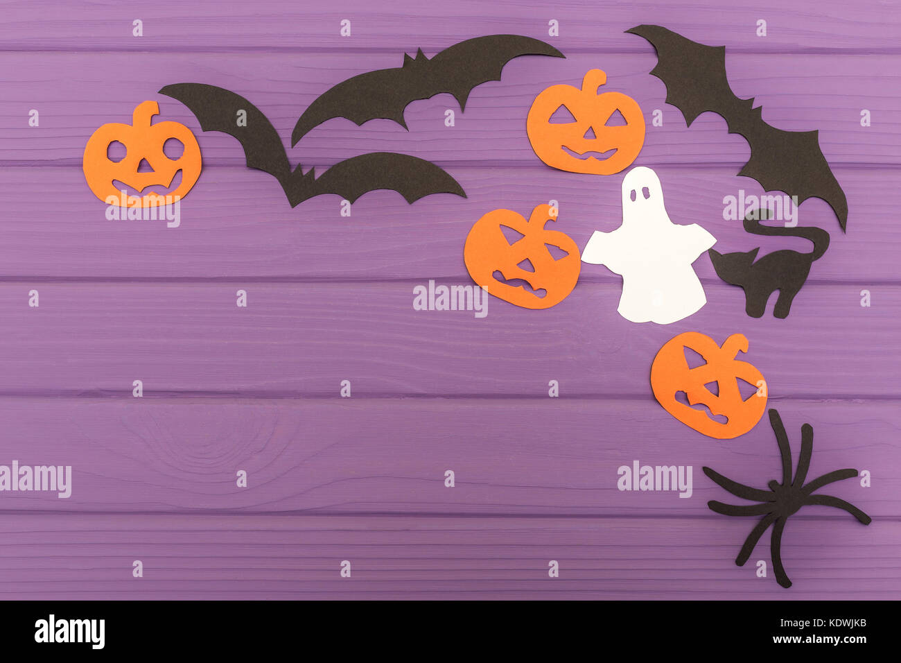 Halloween silhouettes cut out of paper made of corner frame with pumpkins, bats, cat, spider, and ghost on purple - Stock Image