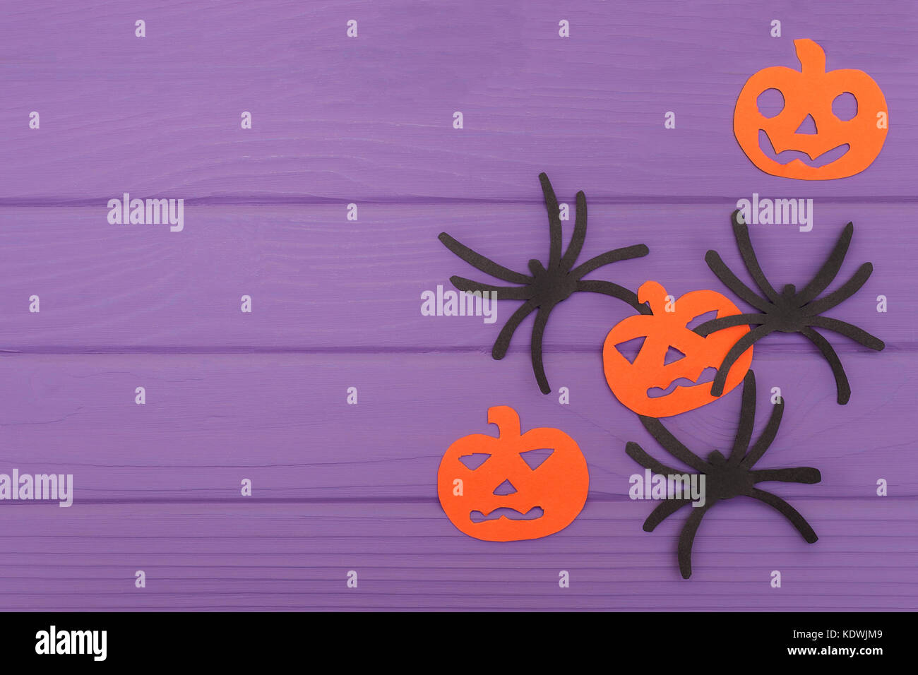 The spiders and pumpkins halloween silhouettes cut out of paper on purple wooden board. Halloween holiday - Stock Image
