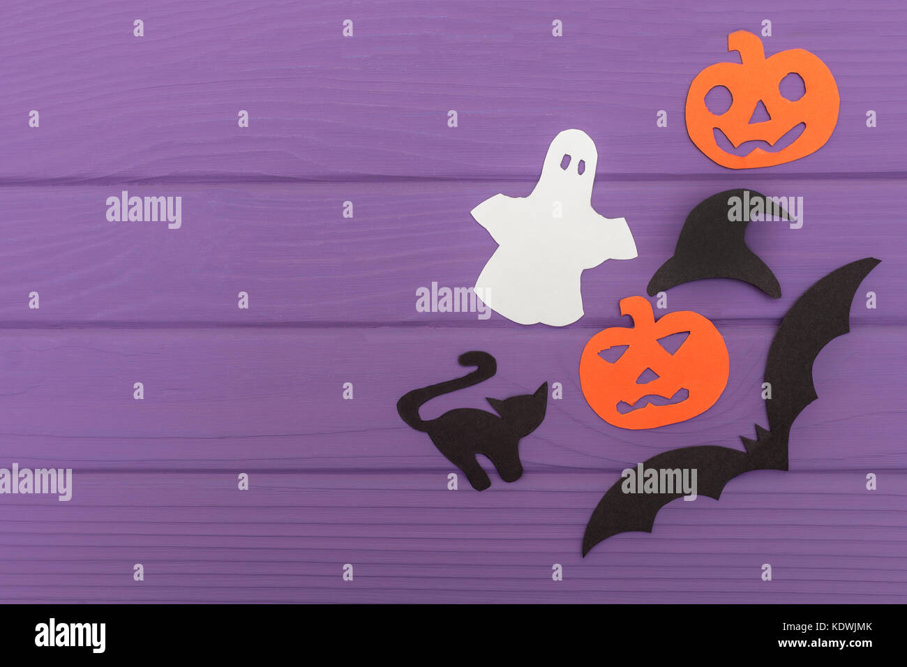 Halloween silhouettes cut out of paper made of corner frame with pumpkins, bat, cat, ghost, hat on purple board. - Stock Image