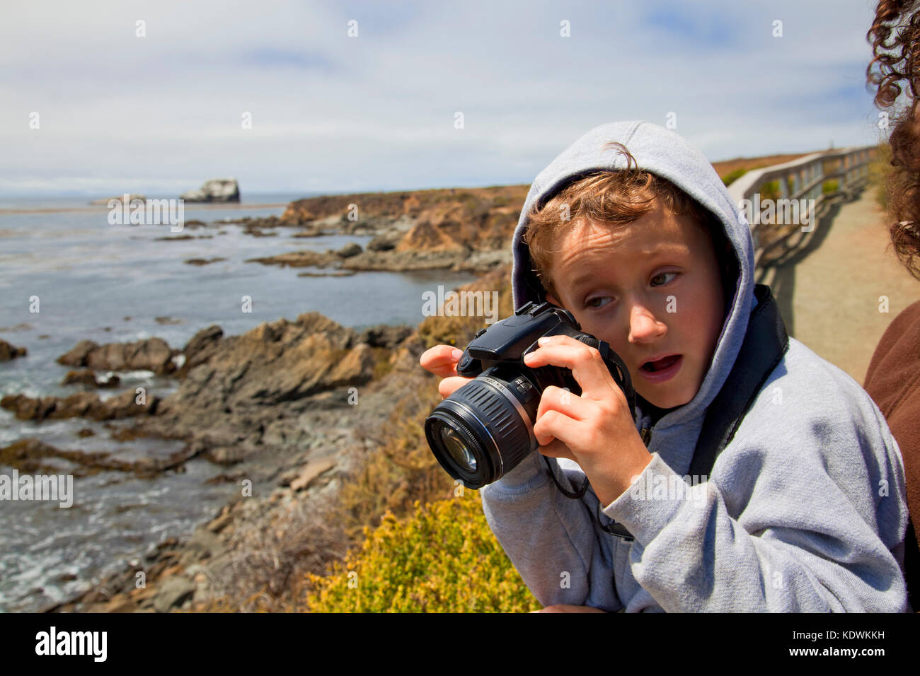 Young boy taking photos with a camera, San Simeon, San Luis Obispo County, California, USA (MR) - Stock Image