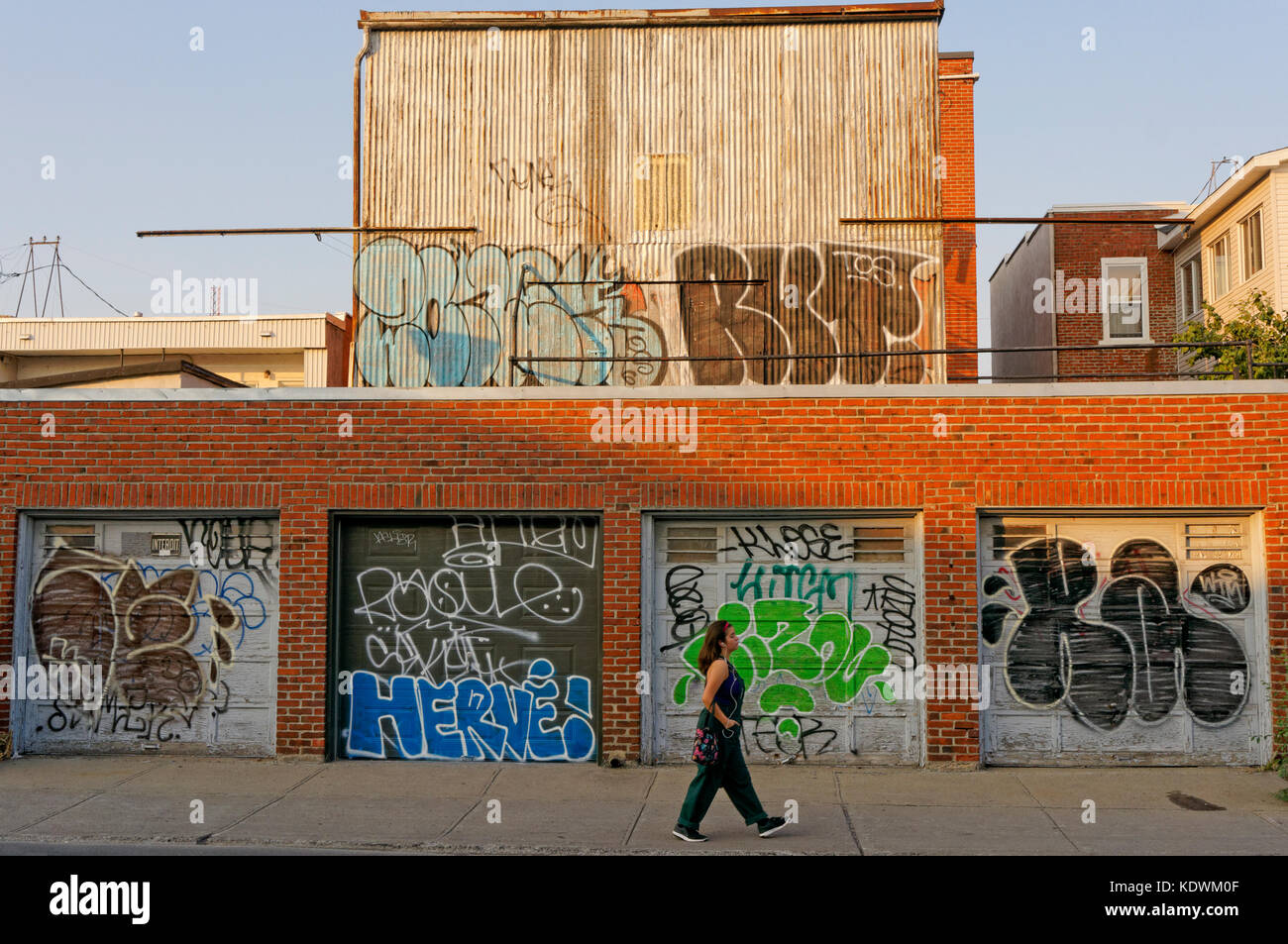 Young woman wearing headphones walking past defaced garage doors and a building covered in urban graffiti and tags, - Stock Image