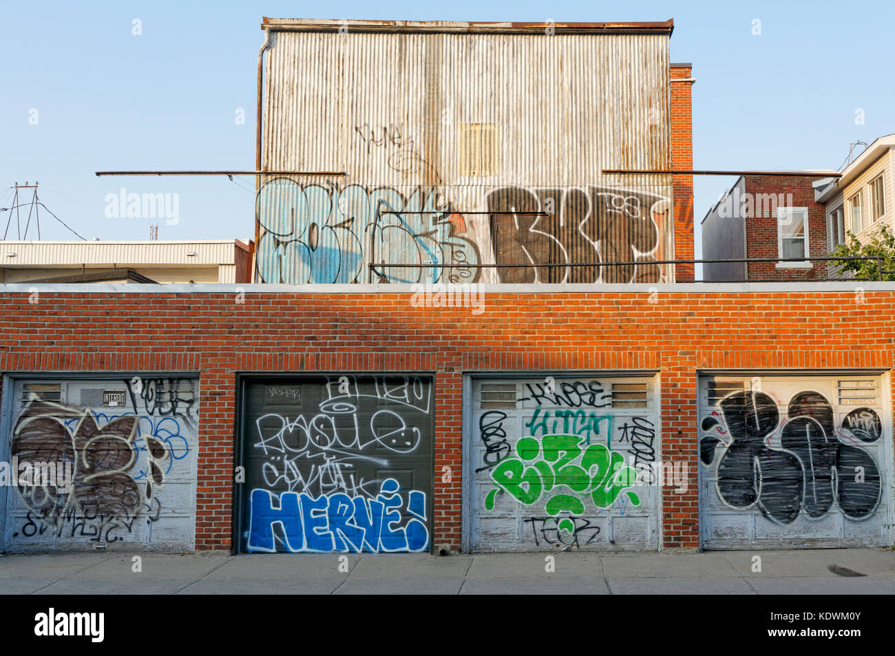 Garage doors and a defaced building covered in urban graffiti and tags, Montreal, Quebec, Canada - Stock Image