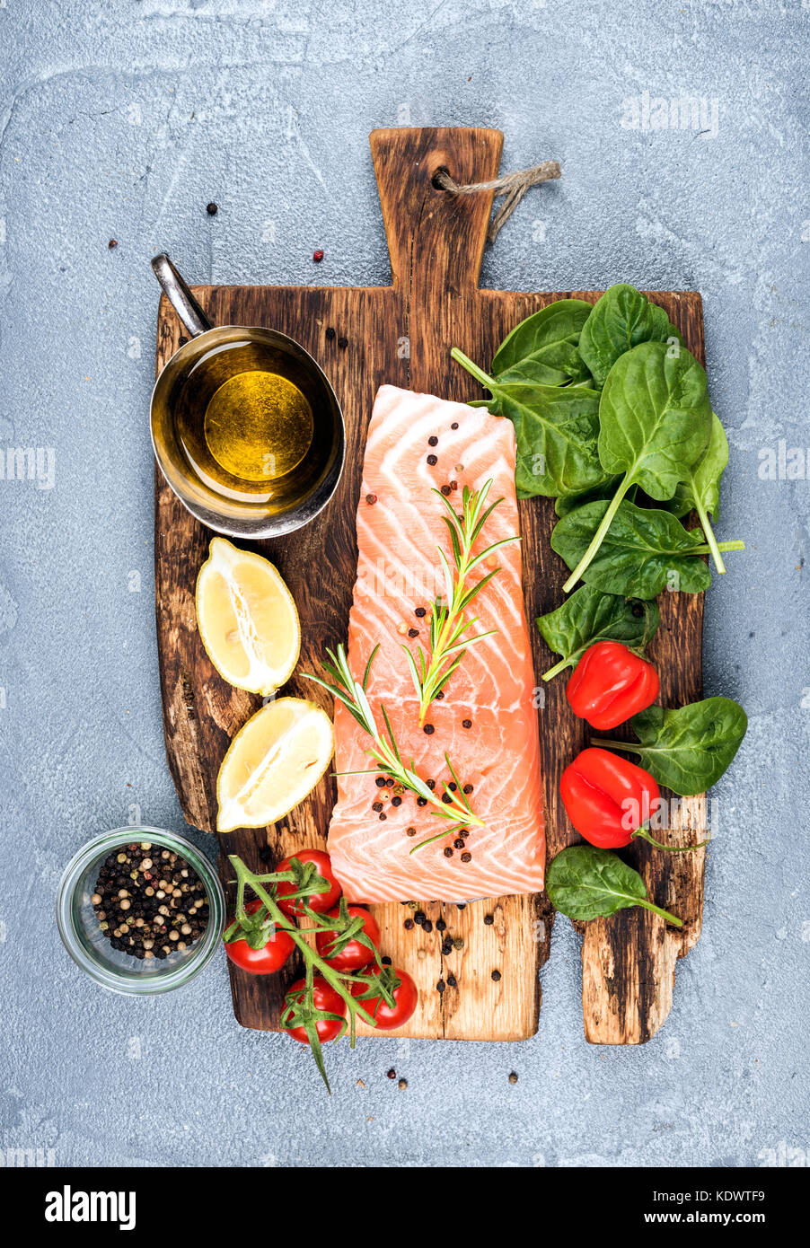 Ingredients for cooking healthy dinner. Raw salmon fillet, spinach, tomatoes, olive oil, lemon, peppers, rosemary - Stock Image