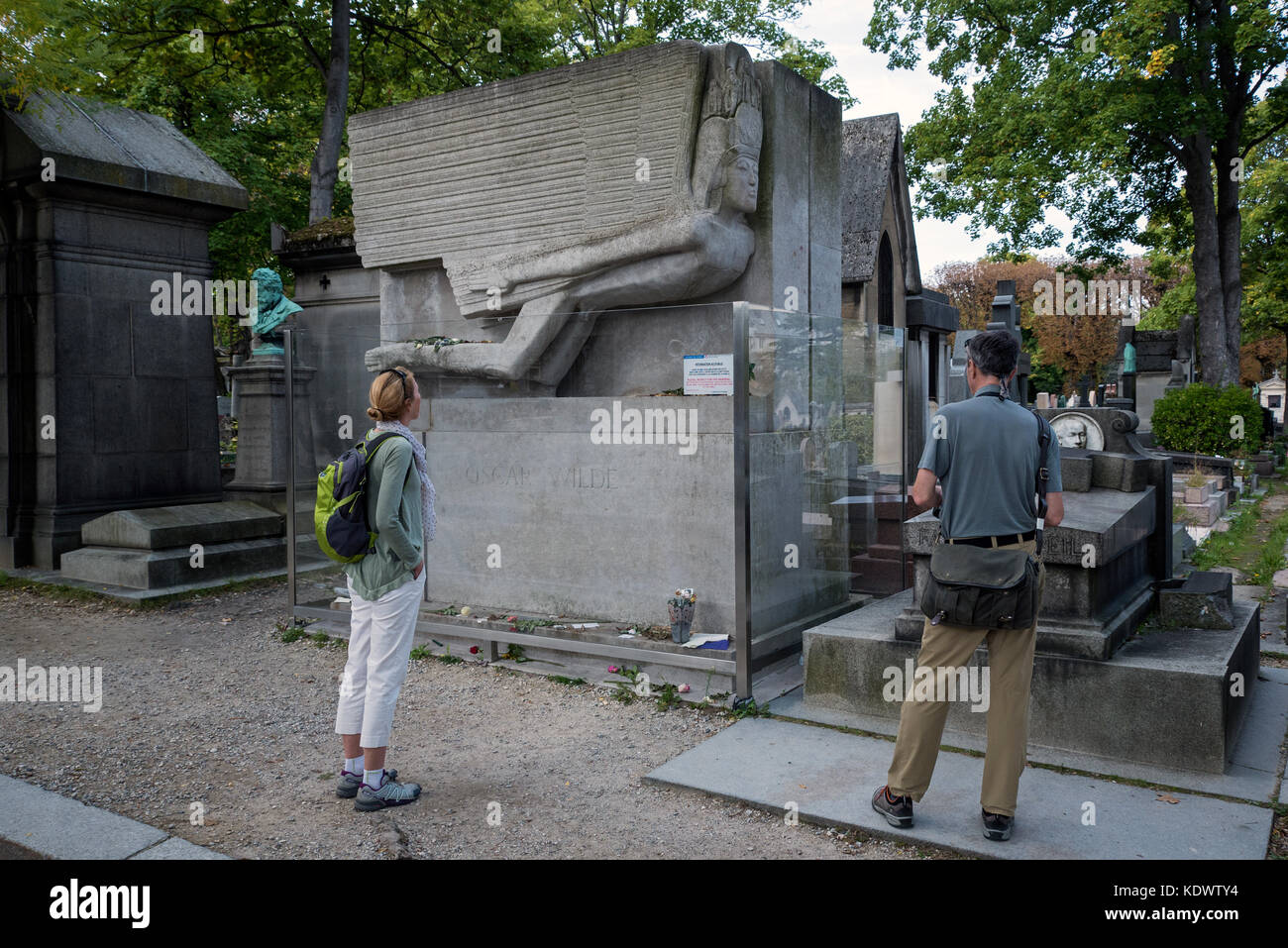 Tourists visit the grave of Oscar Wilde in Pere Lachaise cemetery in Paris, France. - Stock Image