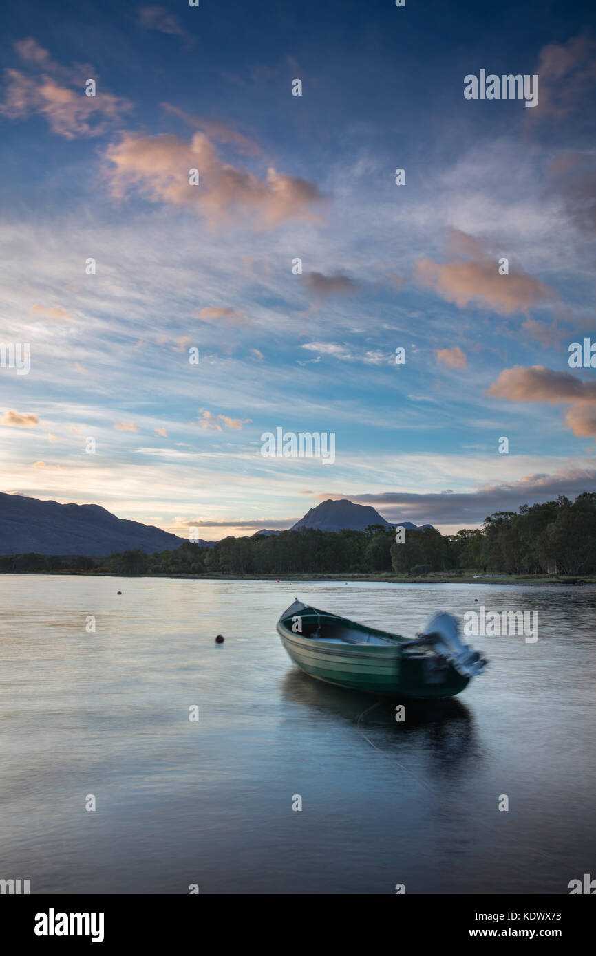 Dawn breaking over a boat moored on Loch Maree, with Slioch beyond, Wester Ross, Scotland - Stock Image