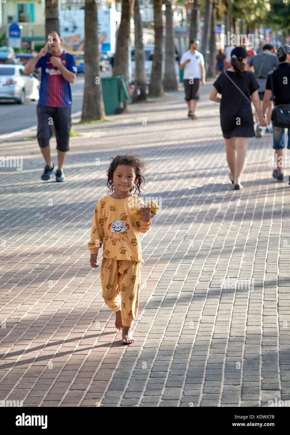 Child alone, playing outside, barefoot, bare feet, street, pavement, sidewalk, Thailand, Southeast Asia - Stock Image