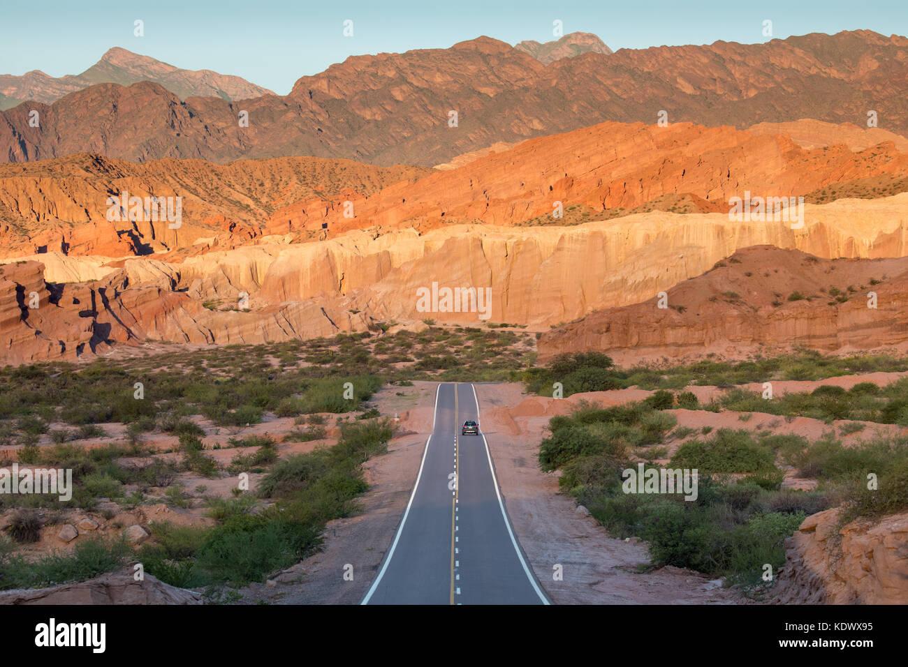 A solitary car on the road down the Quebrada de la Conches, Valles Calchaquies, Salta Province, Argentina - Stock Image