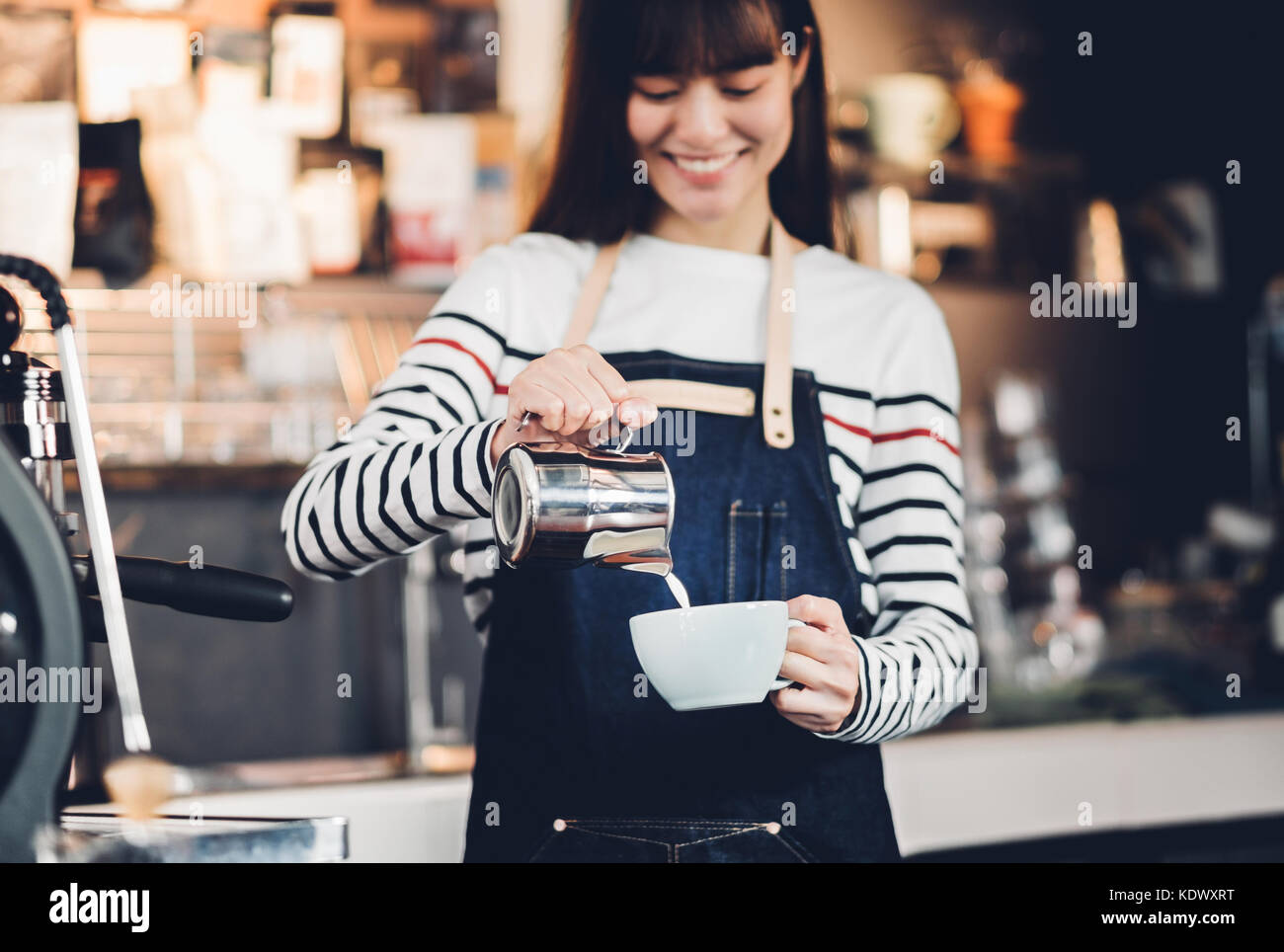 Asia woman barista pour milk into hot coffee cup at counter bar in front of machine in cafe restaurant,Food business - Stock Image