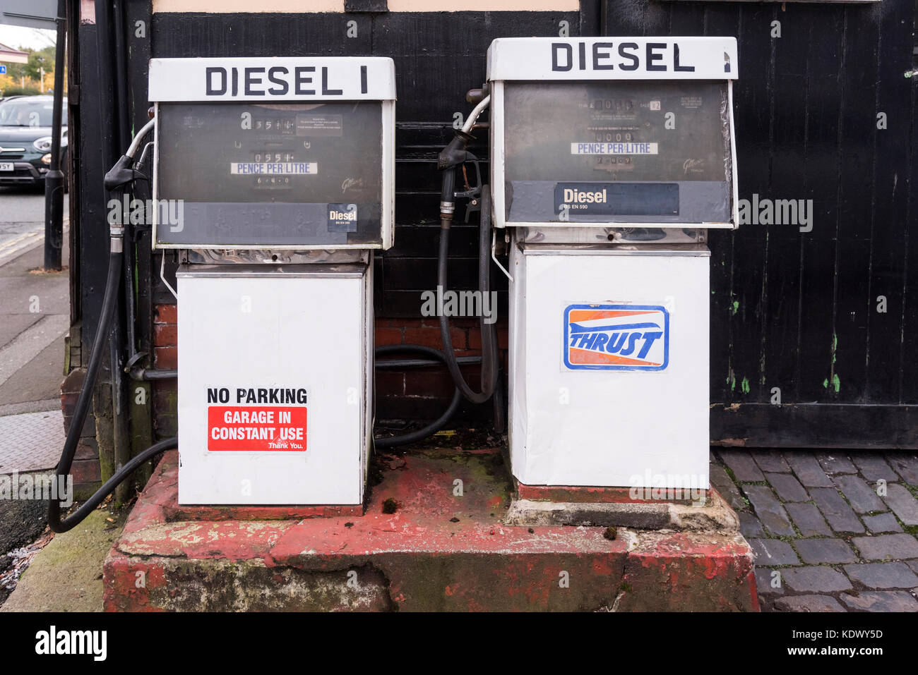 Two old fashion diesel pumps on a garage forecourt. - Stock Image