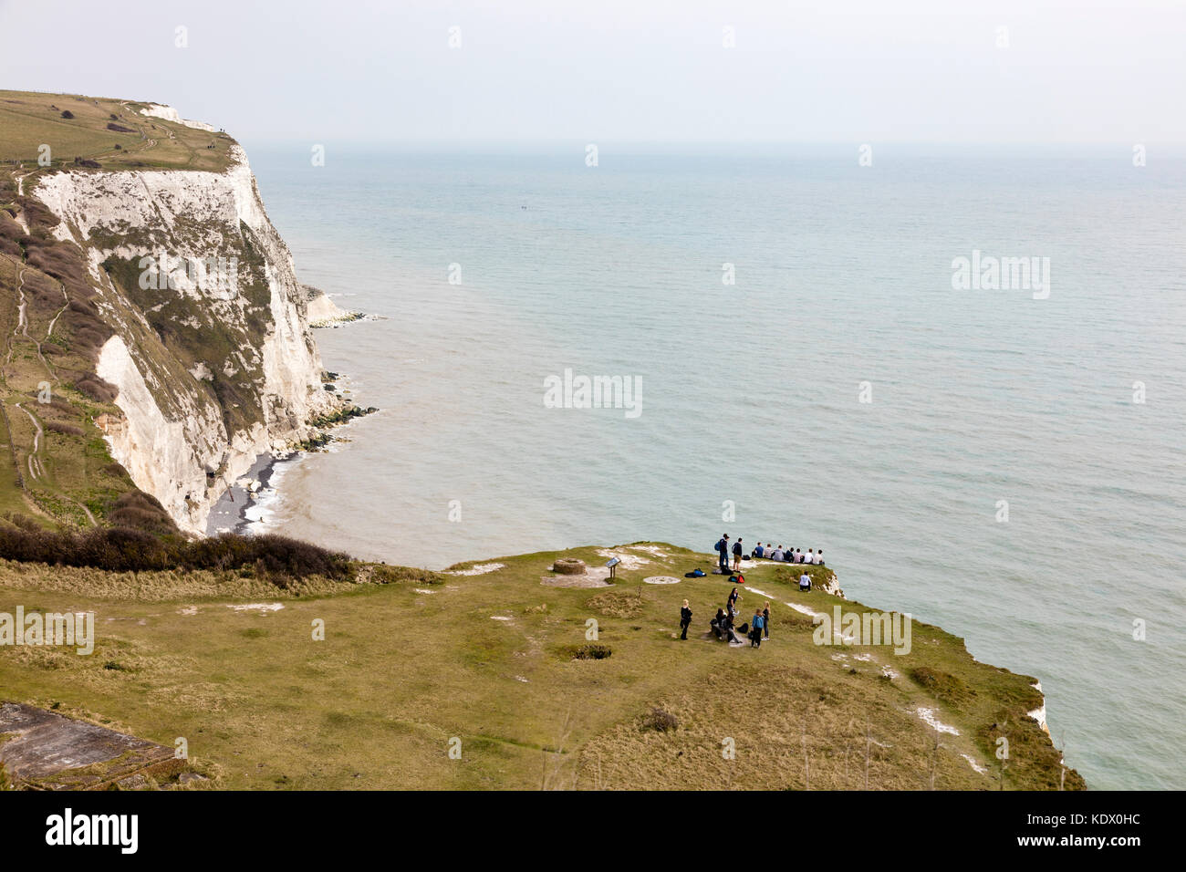 A group of students on the White Cliffs of Dover, Some of them sit dangerously along the edge where chalk falls - Stock Image