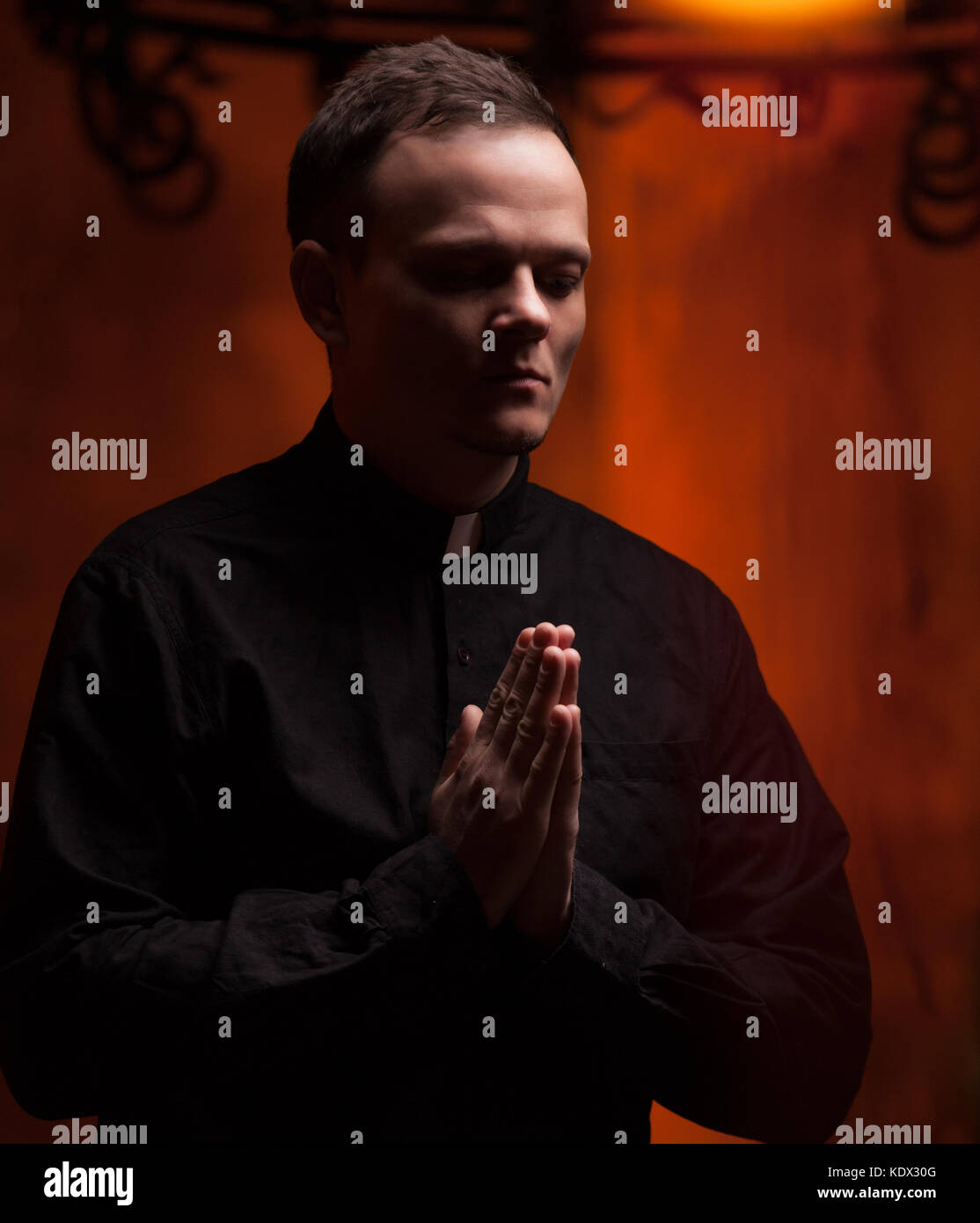 Portrait of handsome catholic priest or pastor with dog collar, dark red background. folded his hands in prayer - Stock Image