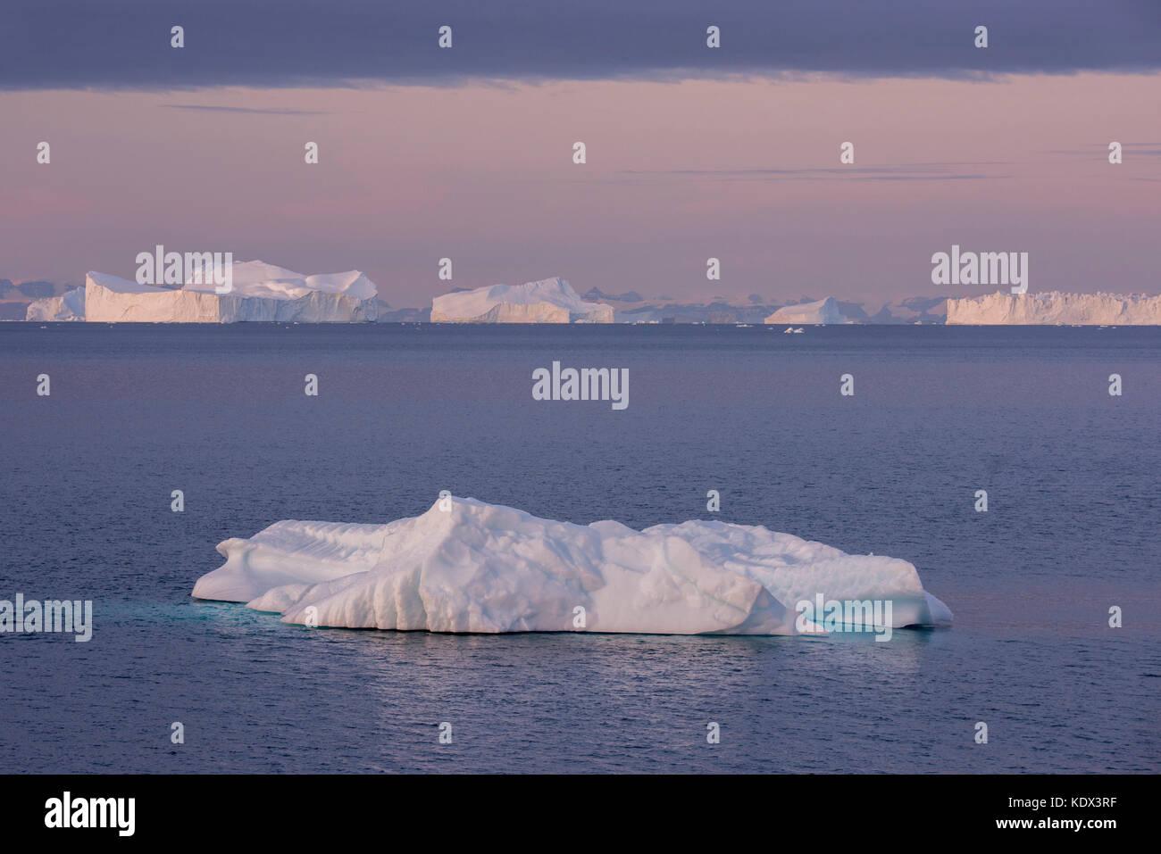 Greenland, Scoresbysund aka Scoresby Sund, Nordvestfjord. Sunrise over huge icebergs. - Stock Image