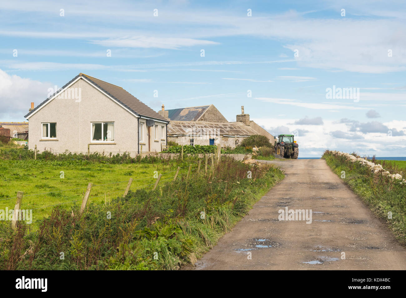 Orkney housing - old and new houses on Westray - modern bungalow, and old stone house with large stone slate roof - Stock Image