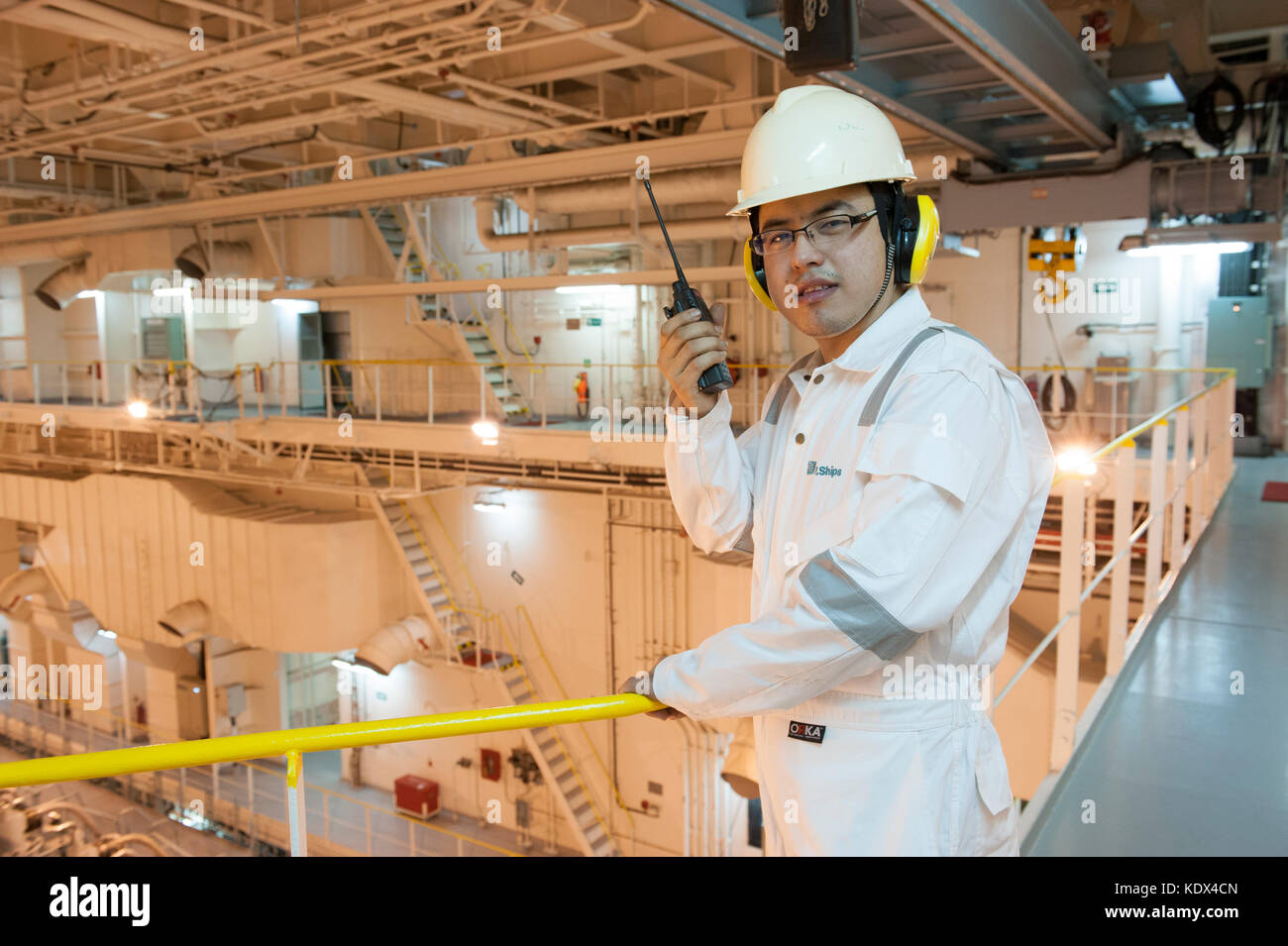 Ship's engineering officer in engine room talking on VHF radio Stock Photo