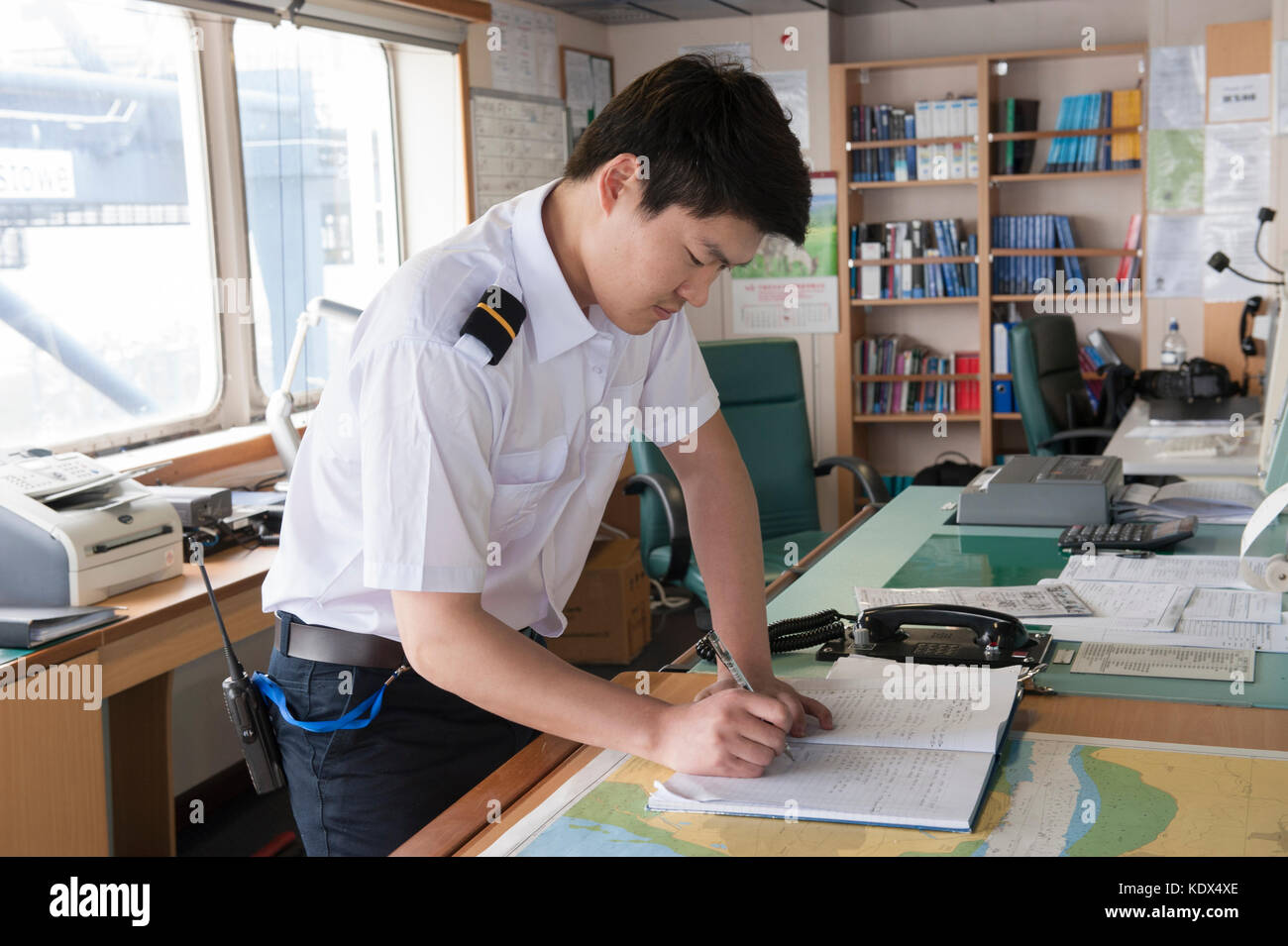 An officer writing navigation notes on a merchant ship - Stock Image