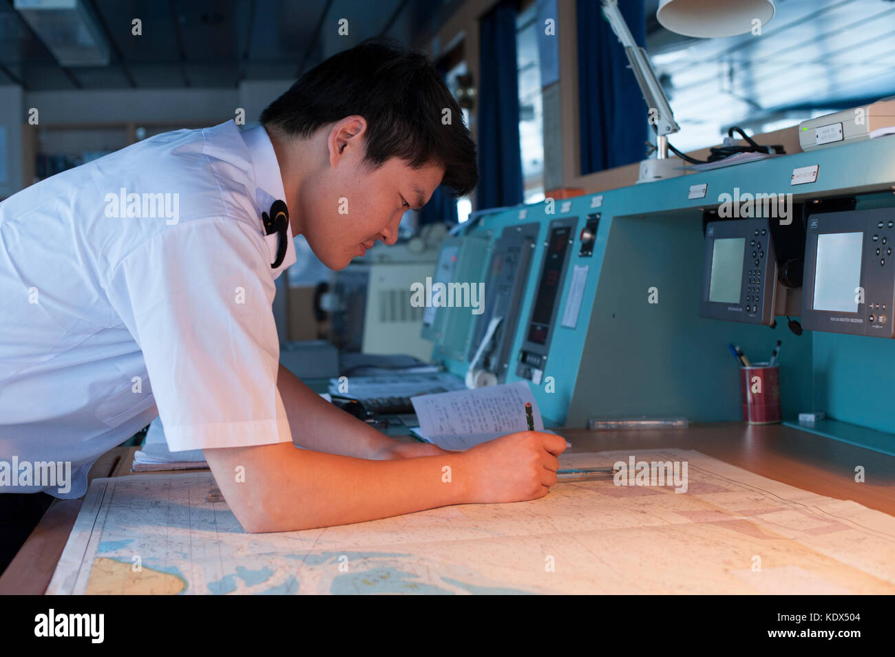 Navigation officer on a merchant ship plotting a course - Stock Image