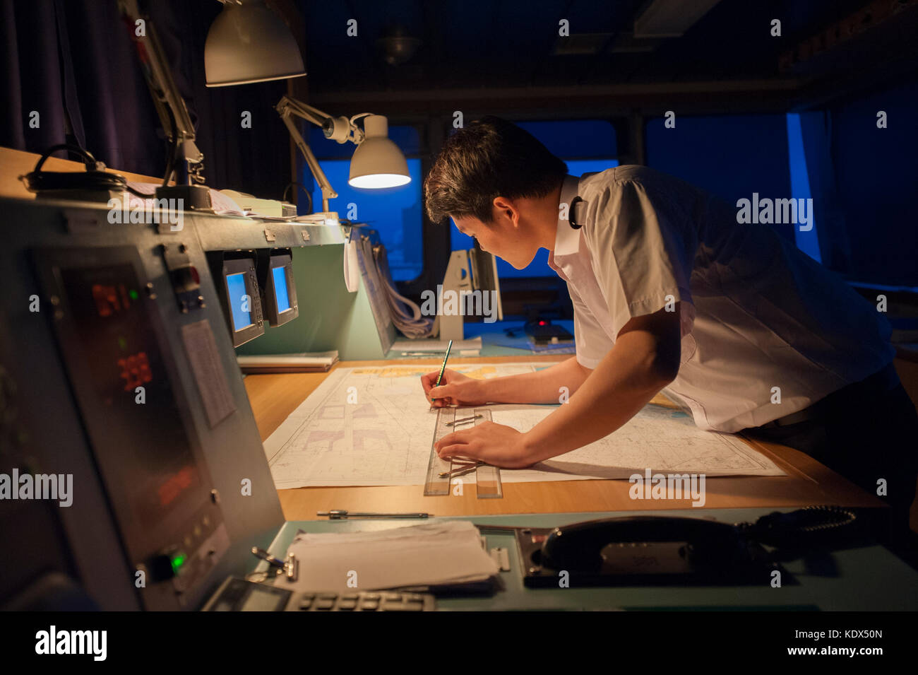 Navigation officer on a merchant ship plotting a course at night - Stock Image