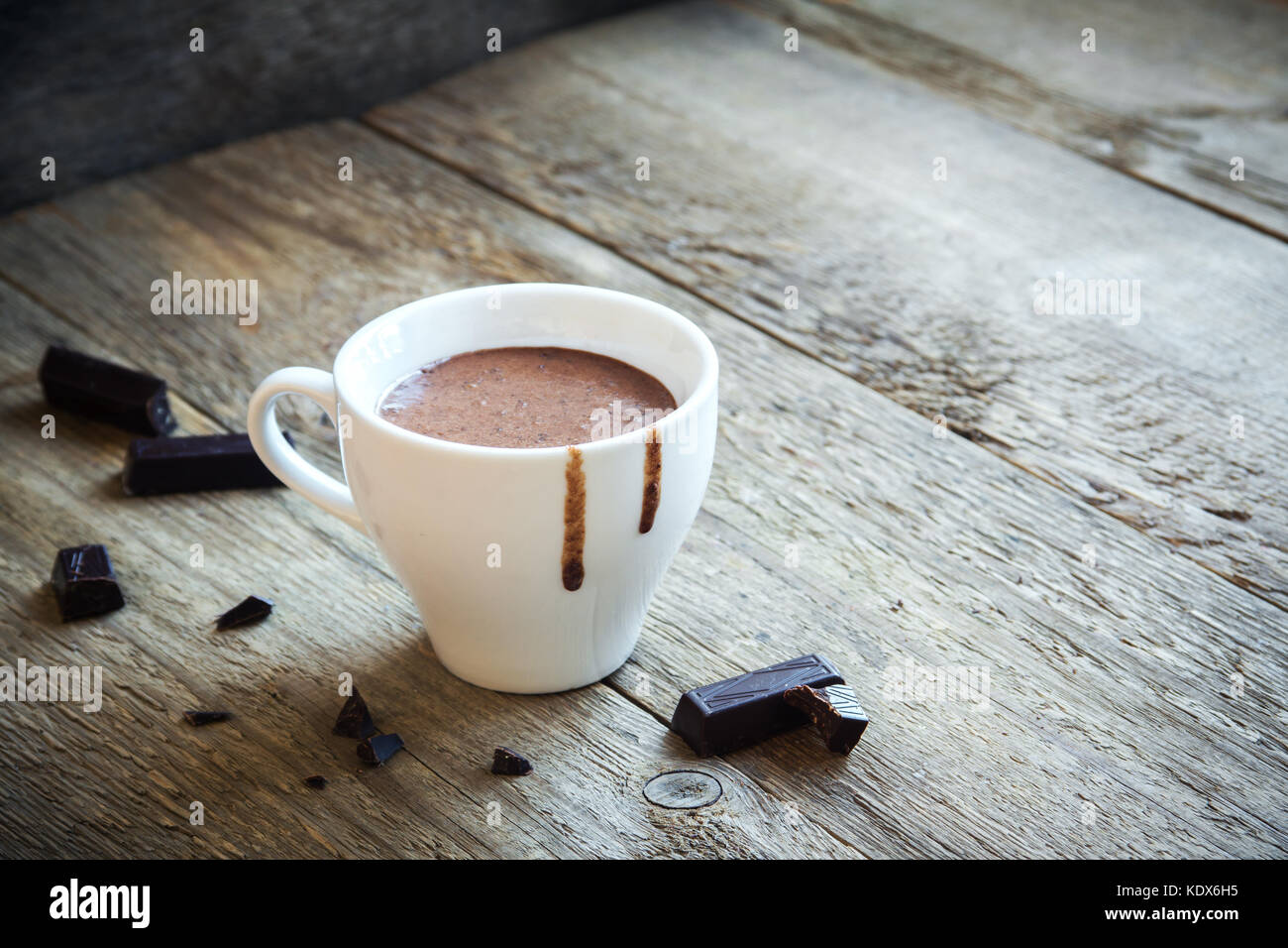 Hot Chocolate and chocolate pieces over rustic wooden background. Homemade Hot Chocolate Drink for Christmas and - Stock Image