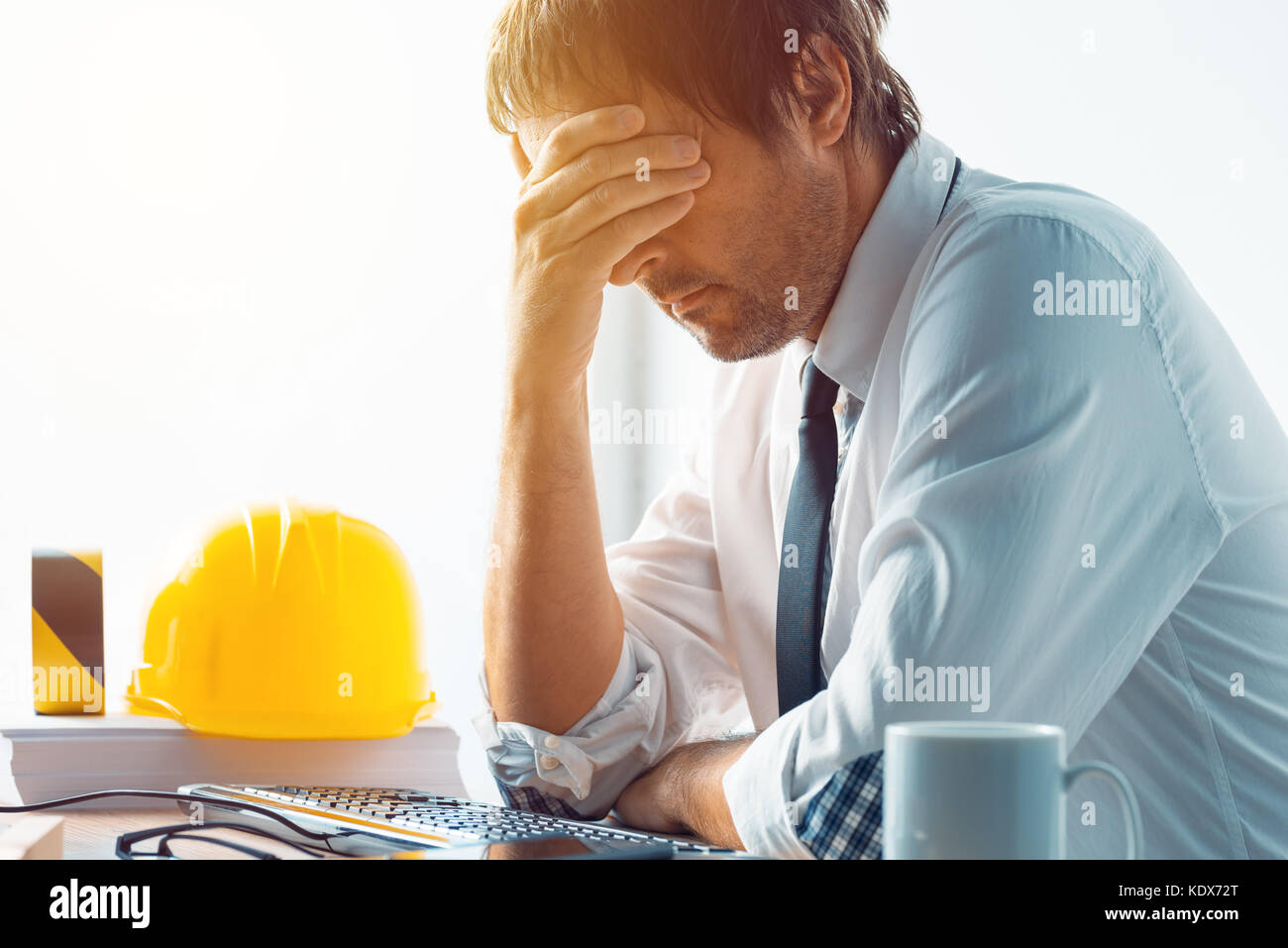 Architect and construction engineer having problems at work in office, construction engineer working with computer - Stock Image