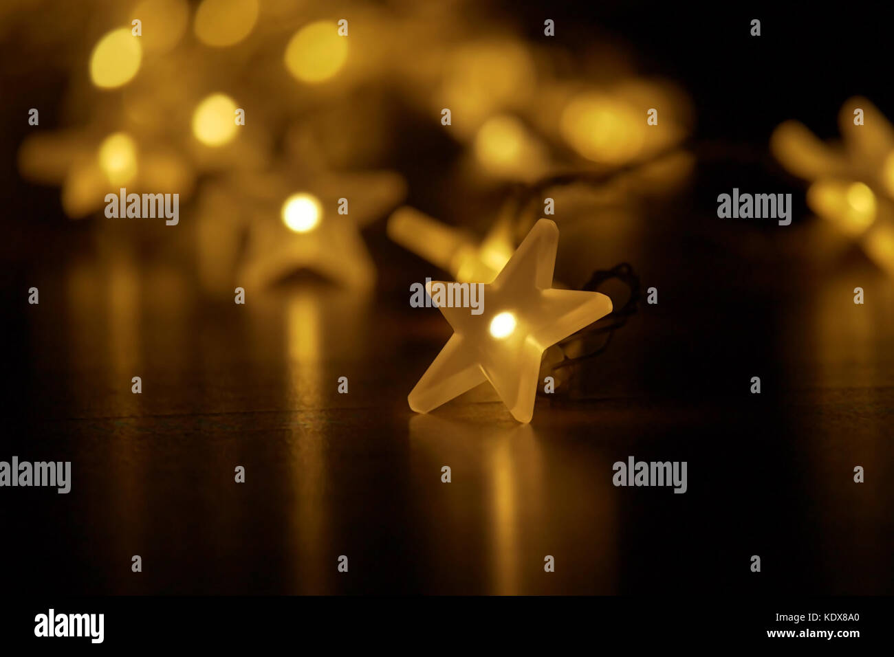 Blaze of lights with festively illuminated light chain; low depth of field on dark background with copy-space - Stock Image