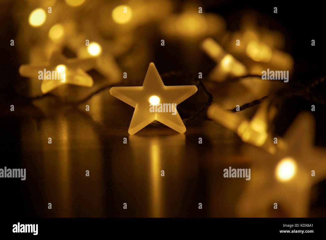 Festive christmas atmosphere with a chain of fairy lights; low depth of field on dark background with copy-space - Stock Image