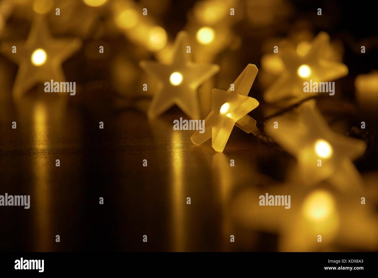 Illuminated chain of starry lights in festive atmosphere; low depth of field on dark background with copy-space - Stock Image